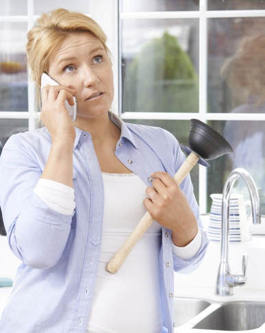 Woman with clogged sink on phone